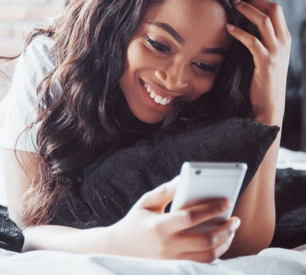Springo - Lady on mobile phone on hotel bed reading SMS message